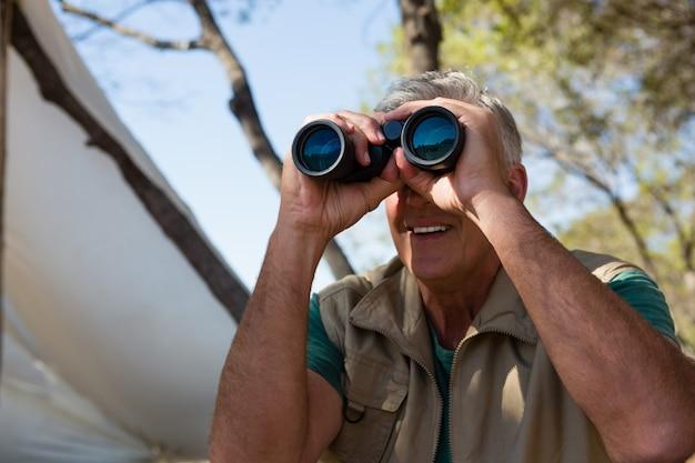 双眼鏡を通して見る中年の男性 無料写真