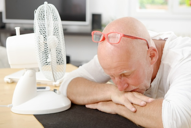 Mature man refreshed with a fan Premium Photo