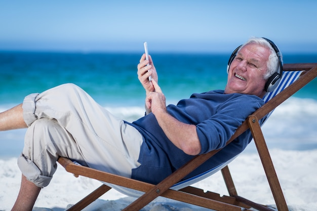 Mature man resting on a deck chair listening to music with smartphone Premium Photo