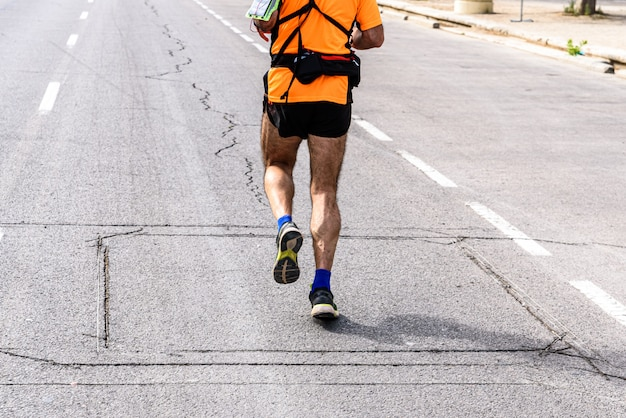 A mature man runner equipped with fanny pack doing sport to exercise his legs running Premium Photo