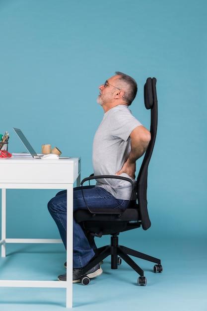 Зрелый человек, сидя в кресле, страдает от боли в спине при использовании на ноутбуке Premium Фотографии