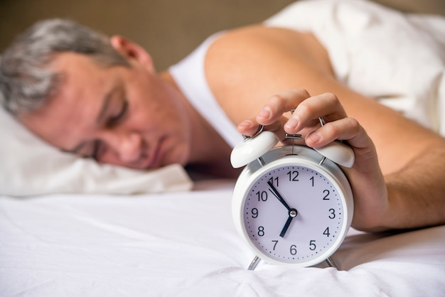 Mature man sleeping in bed with alarm clock in foreground at ...