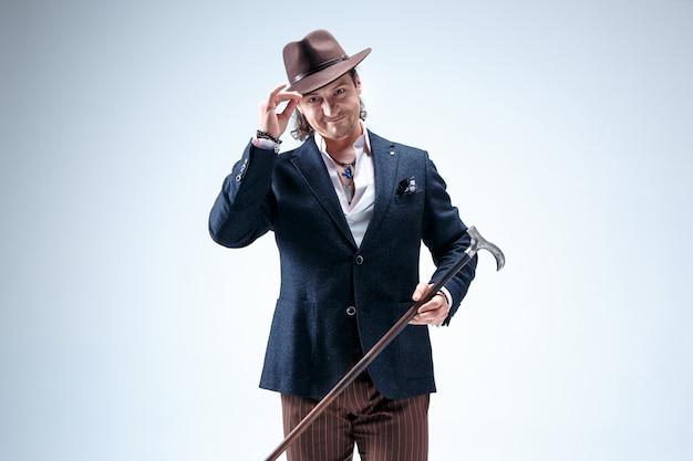 L'uomo maturo in giacca e cappello con canna. isolato su un grigio. Foto Gratuite