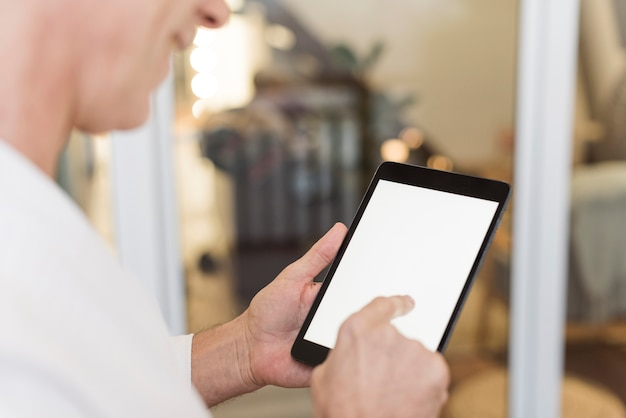 Mature man using a tablet indoors Free Photo