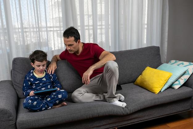 Зрелый мужчина лет сидит рядом со своим сыном лет, положив руку на плечо. Premium Фотографии