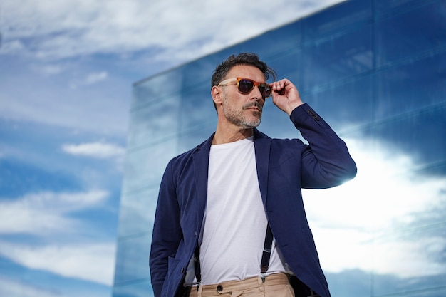 Mature posing with blue jacket and sunglasses Free Photo