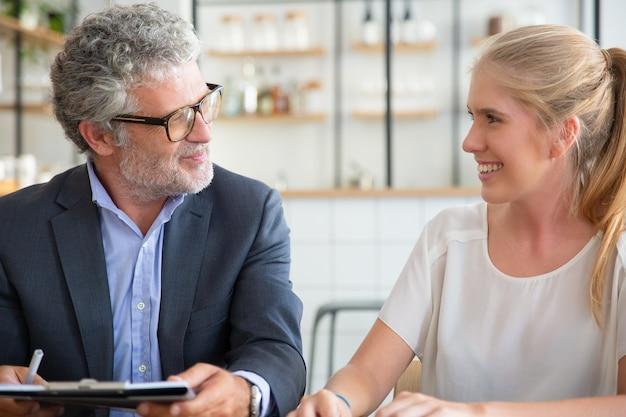 공동 작업에서 젊은 고객과 성숙한 전문 회의, 문서를 들고 이야기하고 웃고 무료 사진