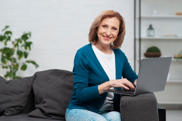 Mature smiley woman using a laptop Free Photo