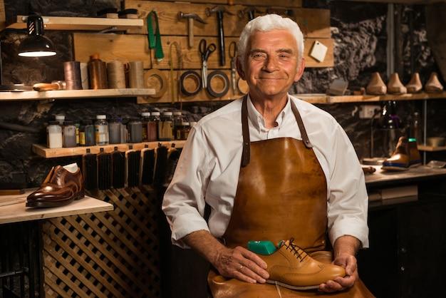 靴を保持しているワークショップで成熟した笑顔の靴屋 無料写真