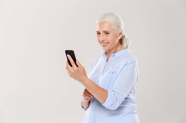 Mature smiling woman using smartphone isolated Free Photo