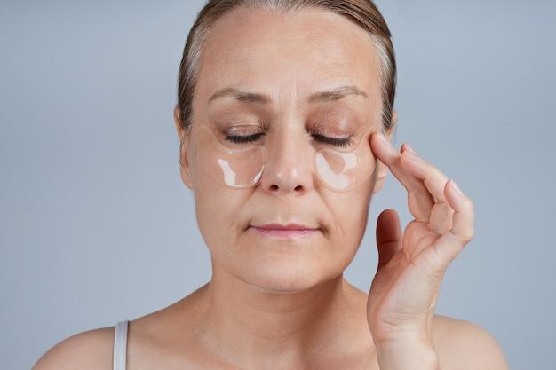 彼女の目の下にパッチを適用する成熟した女性。高齢者のスキンケアに直面します。 Premium写真