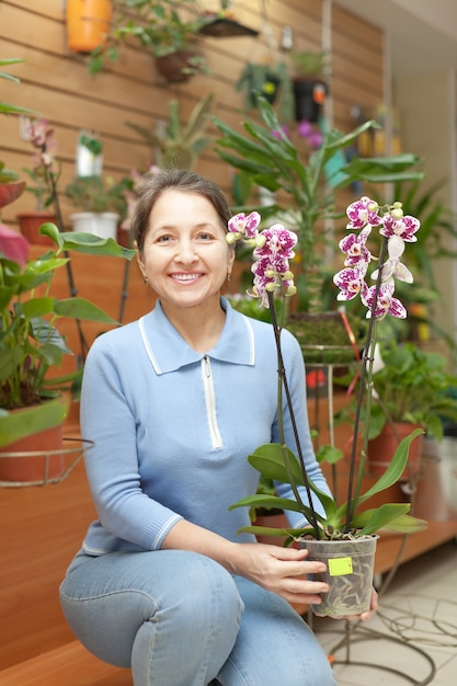 Mature woman chooses  orchid Free Photo