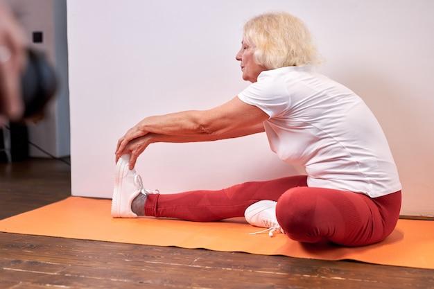 成熟した女性は床で自宅でスポーツ運動をし、腕と脚を伸ばして美しい健康な女性は、ヨガを楽しんで、健康的なライフスタイルをリードします Premium写真