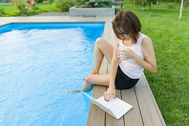 Mature woman freelancer uses aptop sitting by pool Premium Photo