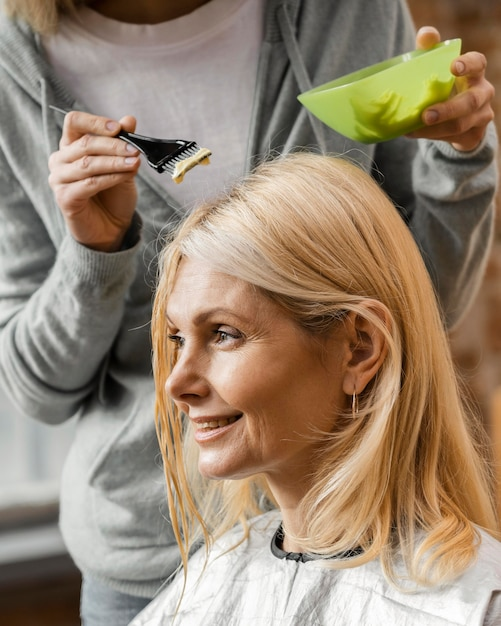 Mature woman getting her hair dyed by hairdresser at home Free Photo