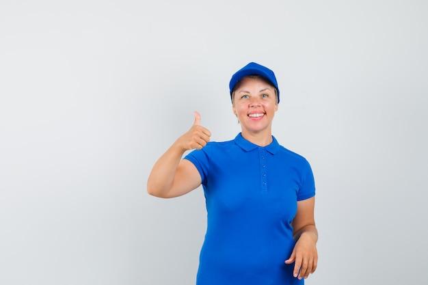 親指を立てて楽観的に見える青いtシャツの成熟した女性 無料写真