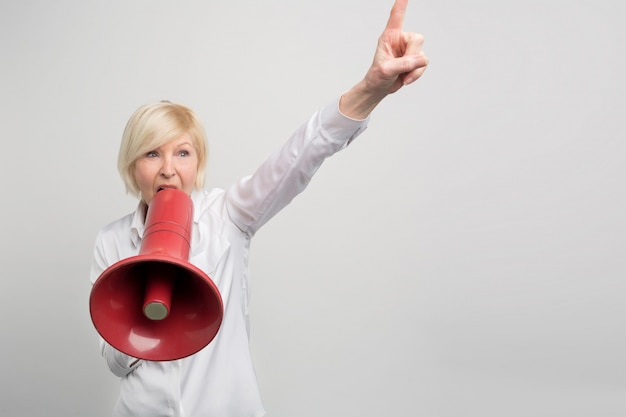 Mature woman is holding a megaphone close to her mouth and screaming into it. she is defending human rights. Premium Photo