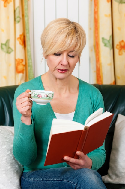 Mature woman is reading a book Premium Photo