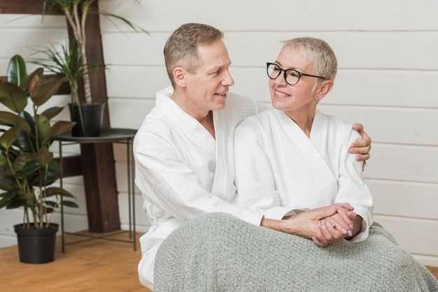 Mature woman and man holding hands indoors Free Photo
