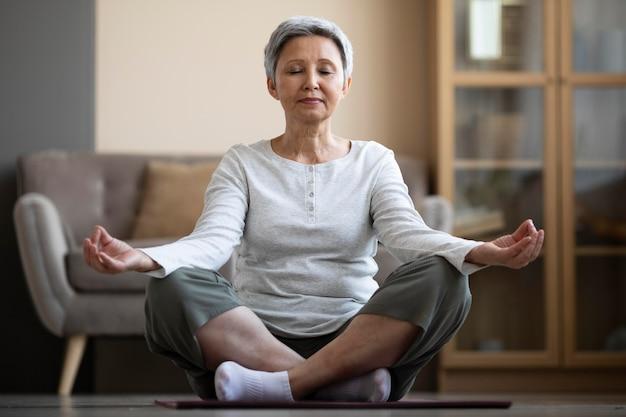 Зрелая женщина медитирует дома Бесплатные Фотографии