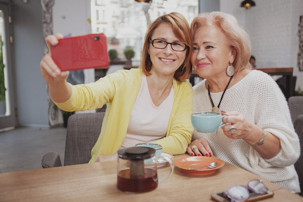 Mature woman meeting her senior mother at the coffee shop Premium Photo