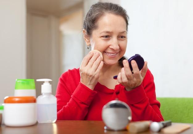 mature woman  puts facepowder Free Photo