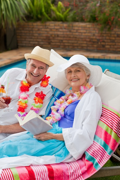 Mature woman reading a book while her husband is drinking a cocktail Premium Photo