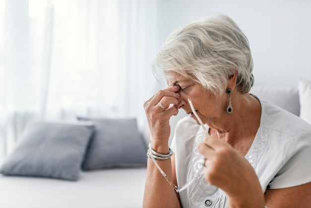 Mature woman sitting on a white sofa in a home touching her head with her hands while havi Premium Photo