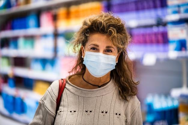 スーパーマーケットでマスクを着用しながらカメラに微笑んで成熟した女性 Premium写真