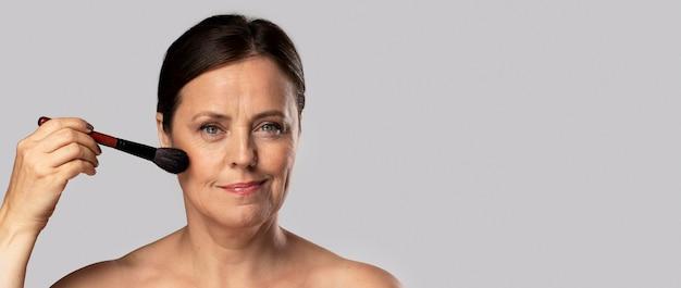 Зрелая женщина с помощью кисти для макияжа на лице с копией пространства Бесплатные Фотографии
