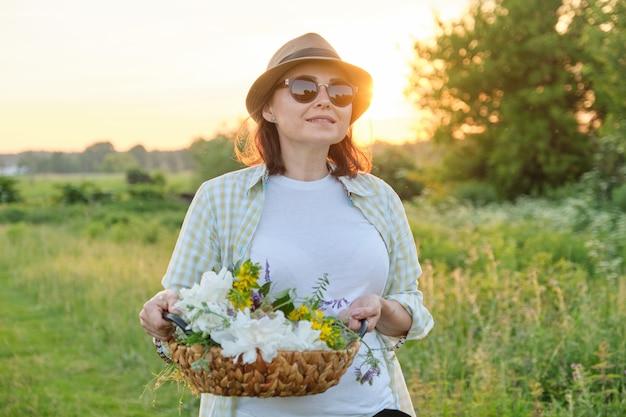 バスケットと花を歩く熟女 Premium写真