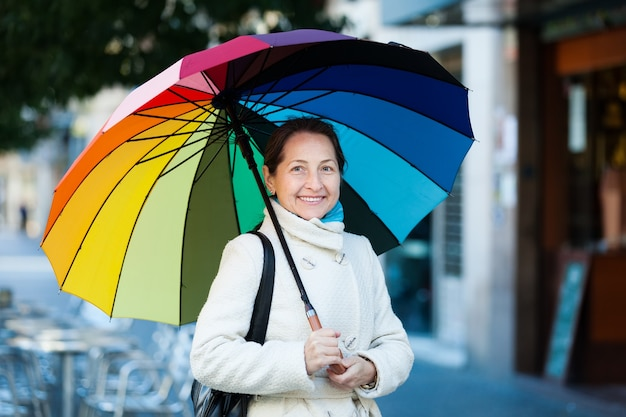 Mature woman with umbrella in autumn Free Photo