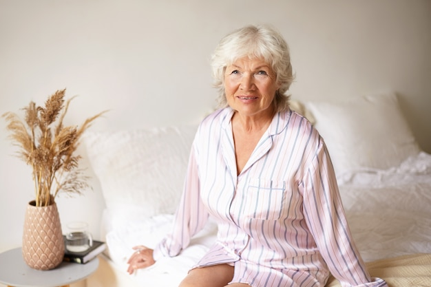 Mature woman with wrinkled skin and gray hair relaxing in bedroom, sitting on bed in silk night gown, looking with charming joyful smile, book, glass of water and dry plant on bedside table Free Photo