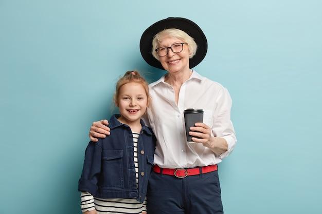 成熟したしわのある祖母と彼女の就学前の赤毛の孫娘は、抱き合って互いに近くに立って、嬉しい笑顔を持ち、持ち帰り用のコーヒーを飲み、良い関係を築いています。生成コンセプト 無料写真