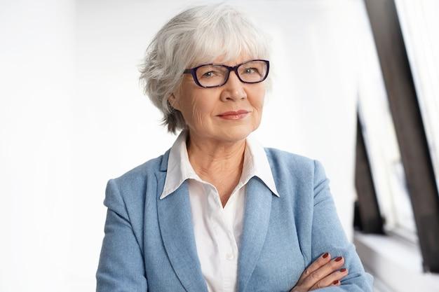 Зрелость, возраст, опыт и пенсионное понятие. уверенная зрелая женщина-генеральный директор, одетая в стильную официальную одежду и очки, скрестившие руки на груди. умная старшая кавказская женщина позирует в помещении Бесплатные Фотографии