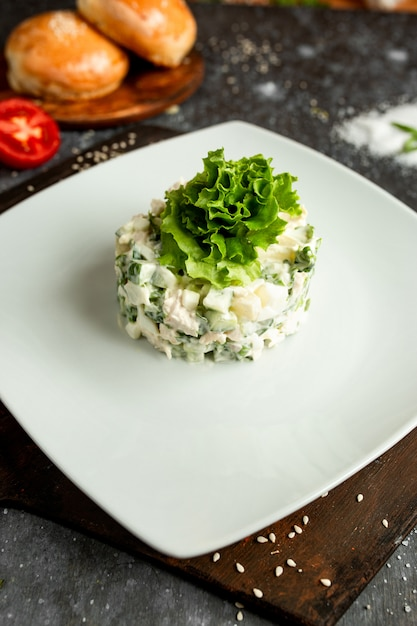 Mayonnaise salad with lettuce on a white plate Photo ...