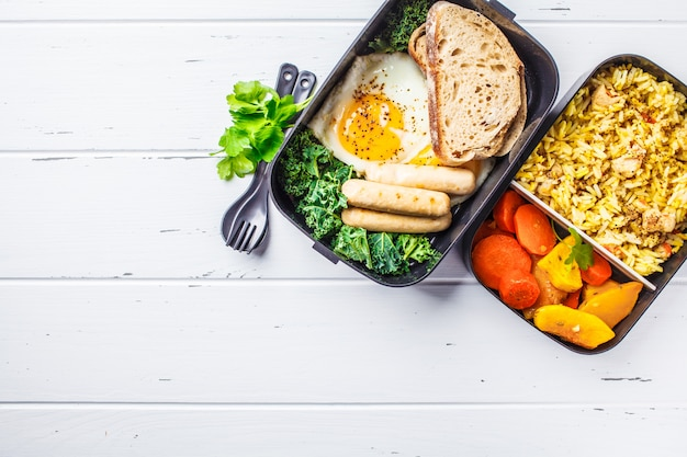 Meal prep containers with rice with chicken, baked vegetables, eggs, sausages and salad overhead shot. Premium Photo