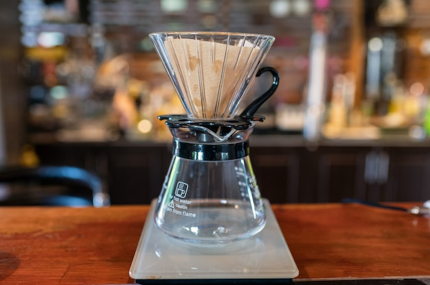 Measuring coffee drip with glass mug and paper filter on counter Premium Photo