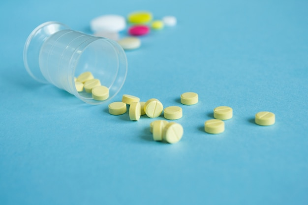 Measuring cup with yellow pills on blue. concept medicine Premium Photo