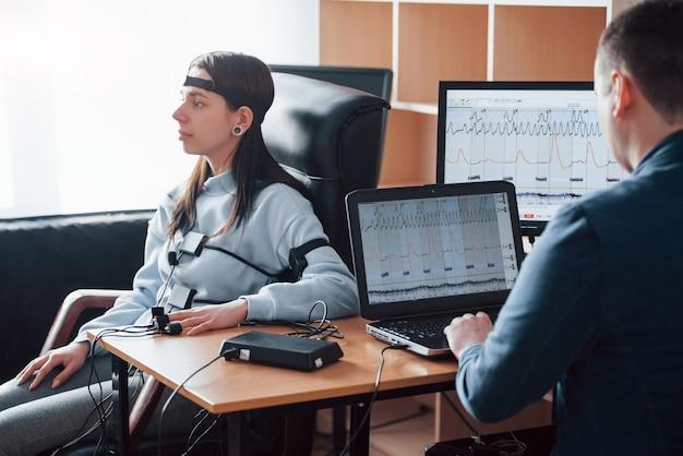 Misurazione della frequenza cardiaca. la ragazza passa la macchina della verità in ufficio. fare domande. test del poligrafo Foto Gratuite