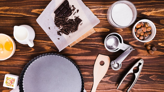 Measuring spoons; chocolate bar; milk; egg yolk; hazelnut and baking dish on wooden textured background Free Photo