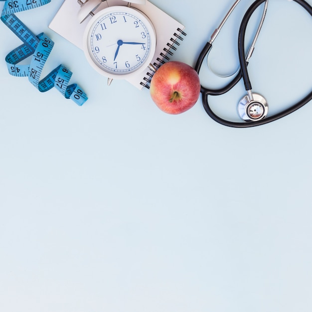Measuring tape; alarm clock; spiral notepad; apple and stethoscope on blue background with copy space for writing the text Free Photo