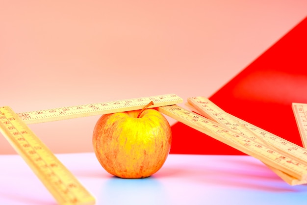 Measuring tape next to an apple, concept of weight loss with healthy diet. Premium Photo