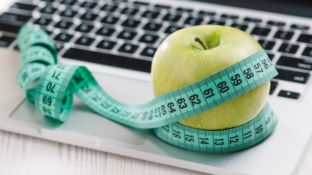Measuring tape around the green fresh apple on an open laptop Free Photo