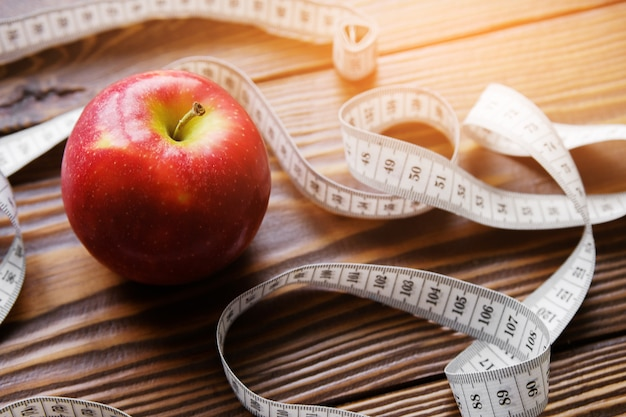 Measuring tape and red apple. the concept of diet, healthy lifestyle and proper nutrition. Premium Photo