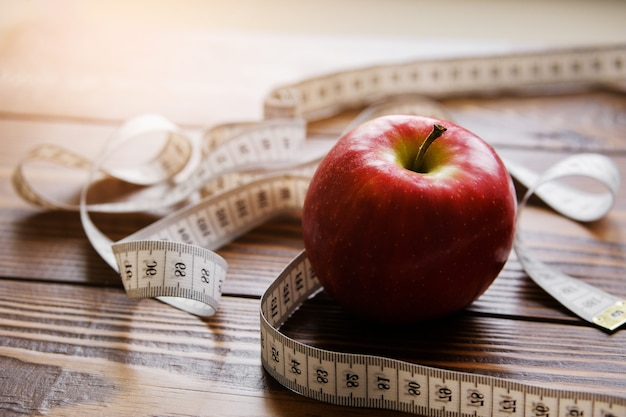 Measuring tape and red apple on wooden background Premium Photo