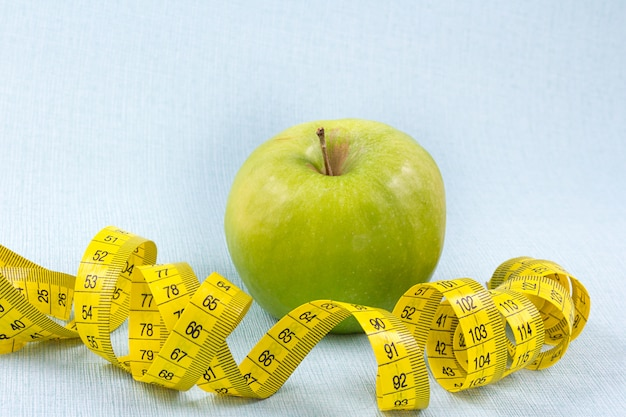 Measuring tape with greem apple on blue background. weight loss concept. Premium Photo