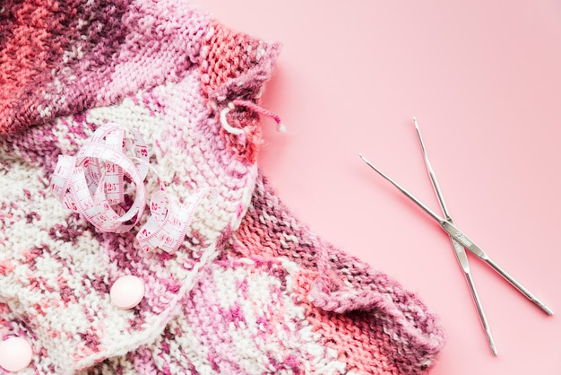 Measuring tape with knitting crochet and needles on pink backdrop Free Photo
