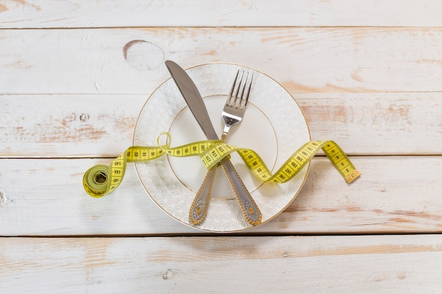 Measuring tape on a wooden background. diet concept Premium Photo