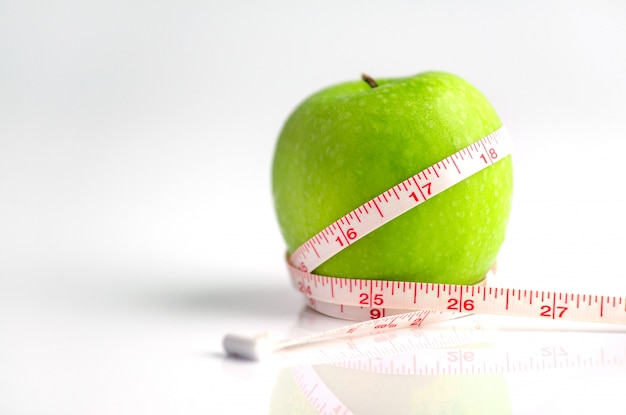 Measuring tape wrapped around a green apple as a symbol of diet Premium Photo